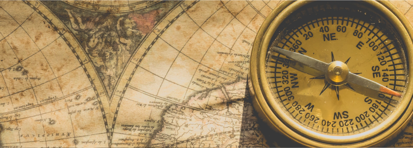 old style yellowing world map with an old metal compass